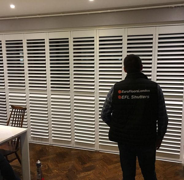 tracked plantation shutters in chelsea home installed by fitter who is looking at the finished product
