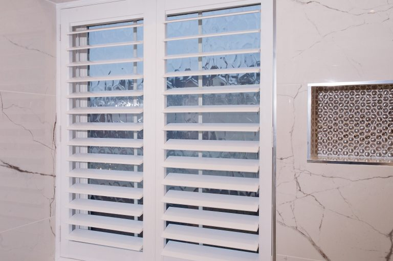 bathroom window covered with interior full height plantation shutters